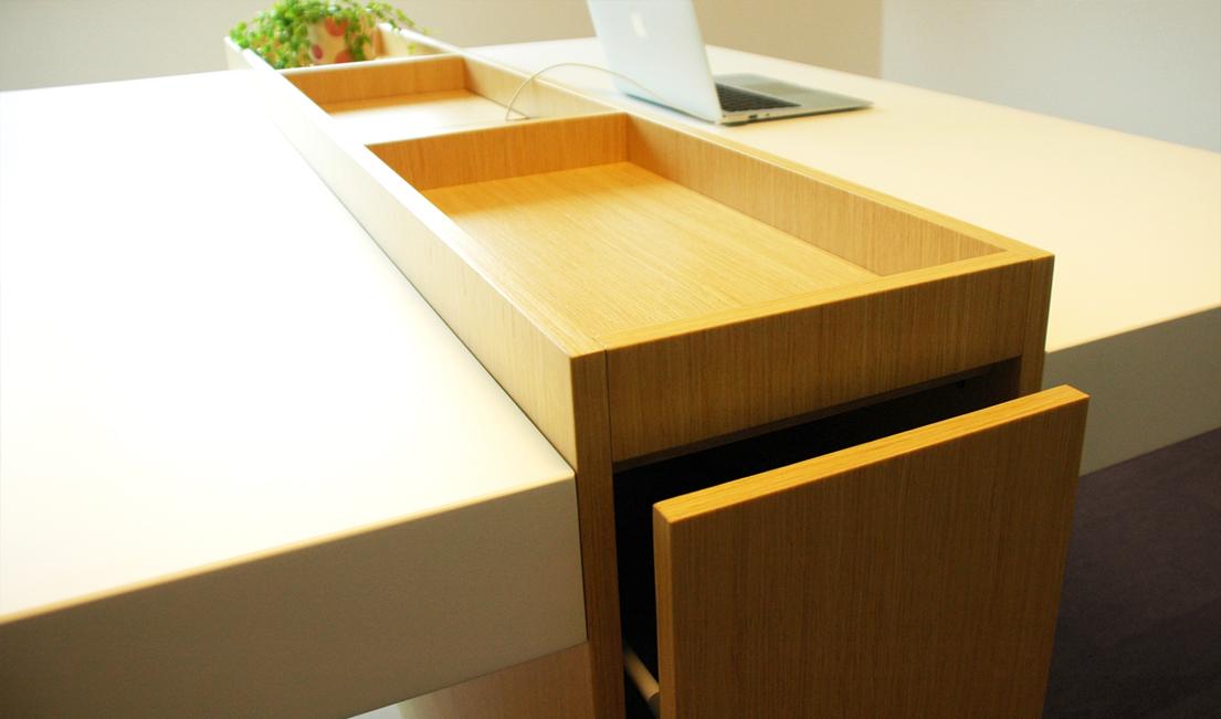 Střed stolu tvoří funkční základna s horním odkládacím prostorem.