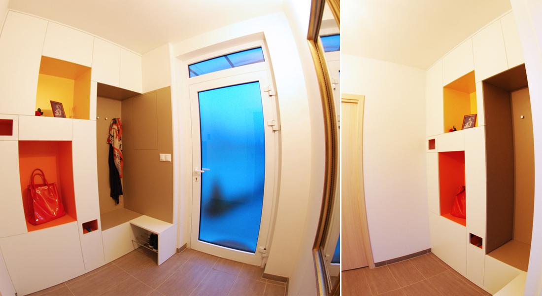 Vchodový blok v sobě ukrývá úložné prostory, botník, přístup pro uzávěr vody a jističe. Díky otevřeným barevným nikám a bílé barvě nepůsobí mohutně. Dle návrhu realizovala firma Tauer Habitat.