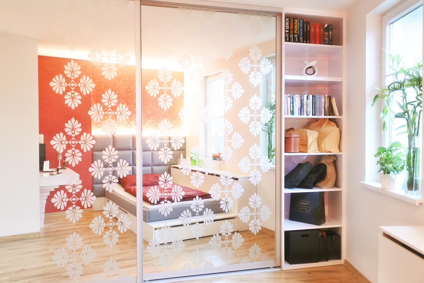 Naproti postele je umístěná vestavná skříň, kterou odlehčuje otevřená policová část. Vypískovaný dekor na zrcadlových dveřích skříně navazuje na dekor červené tapety nad čalouněným čelem postele.