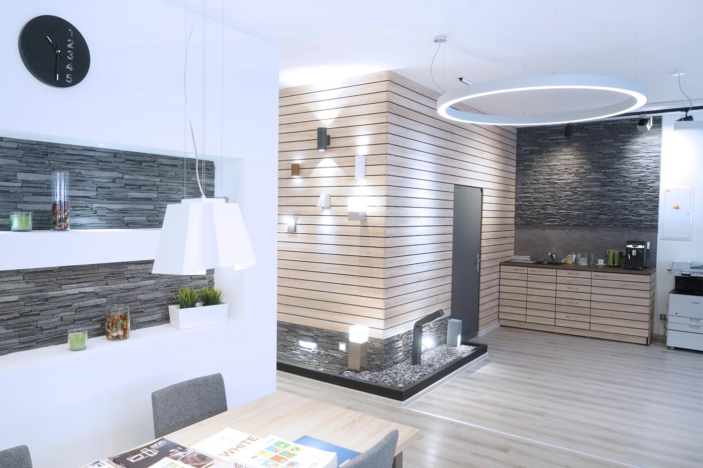 Venkovní a fasádní svítidla jsou prezentovány na zdi podobné moderní fasádě, která přechází do funkční kuchyňky.