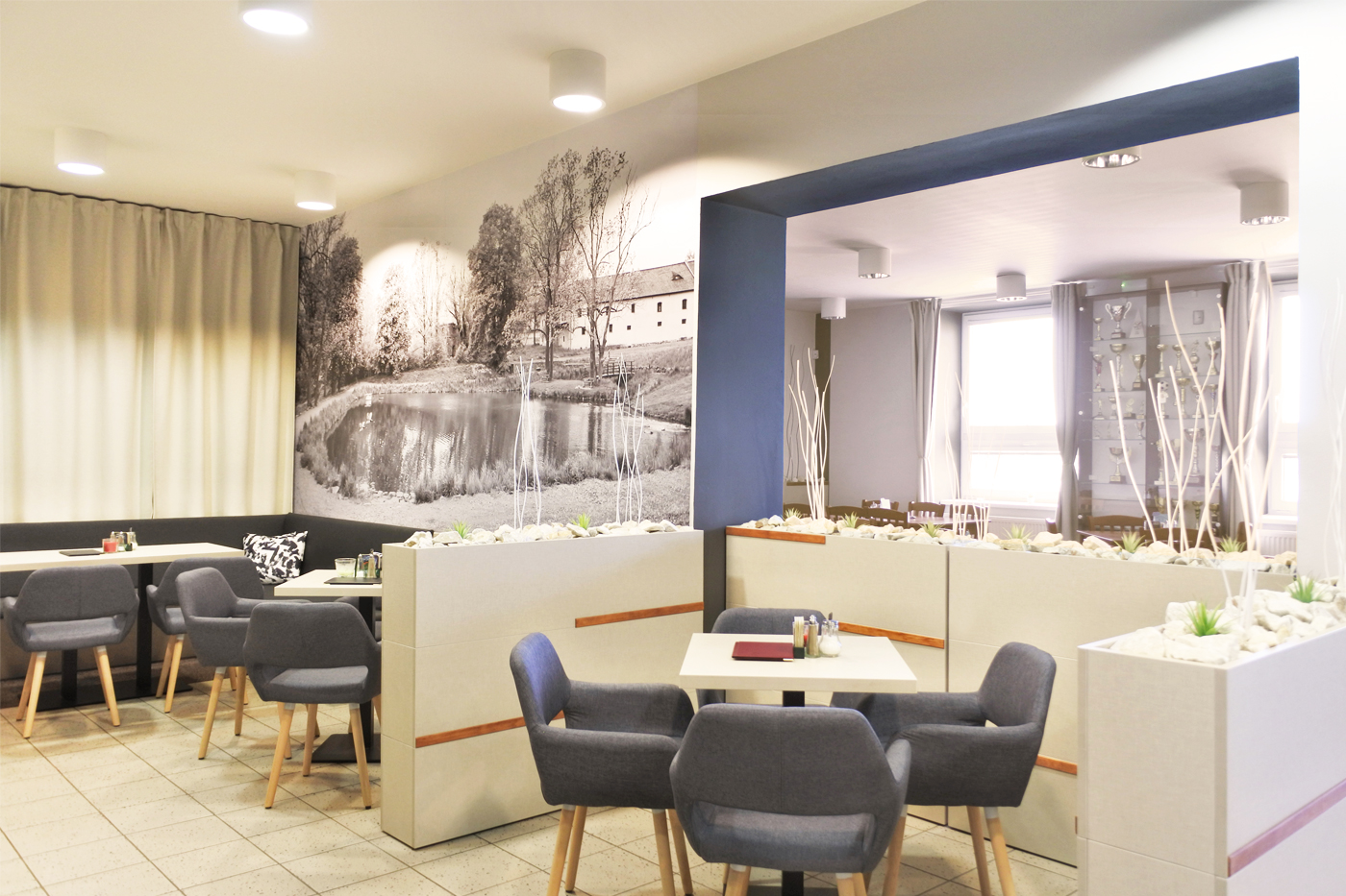 V méně využívané části vzniklo posezení kavárenského stylu oddělené vysokými truhlíky s dekorativními prvky.