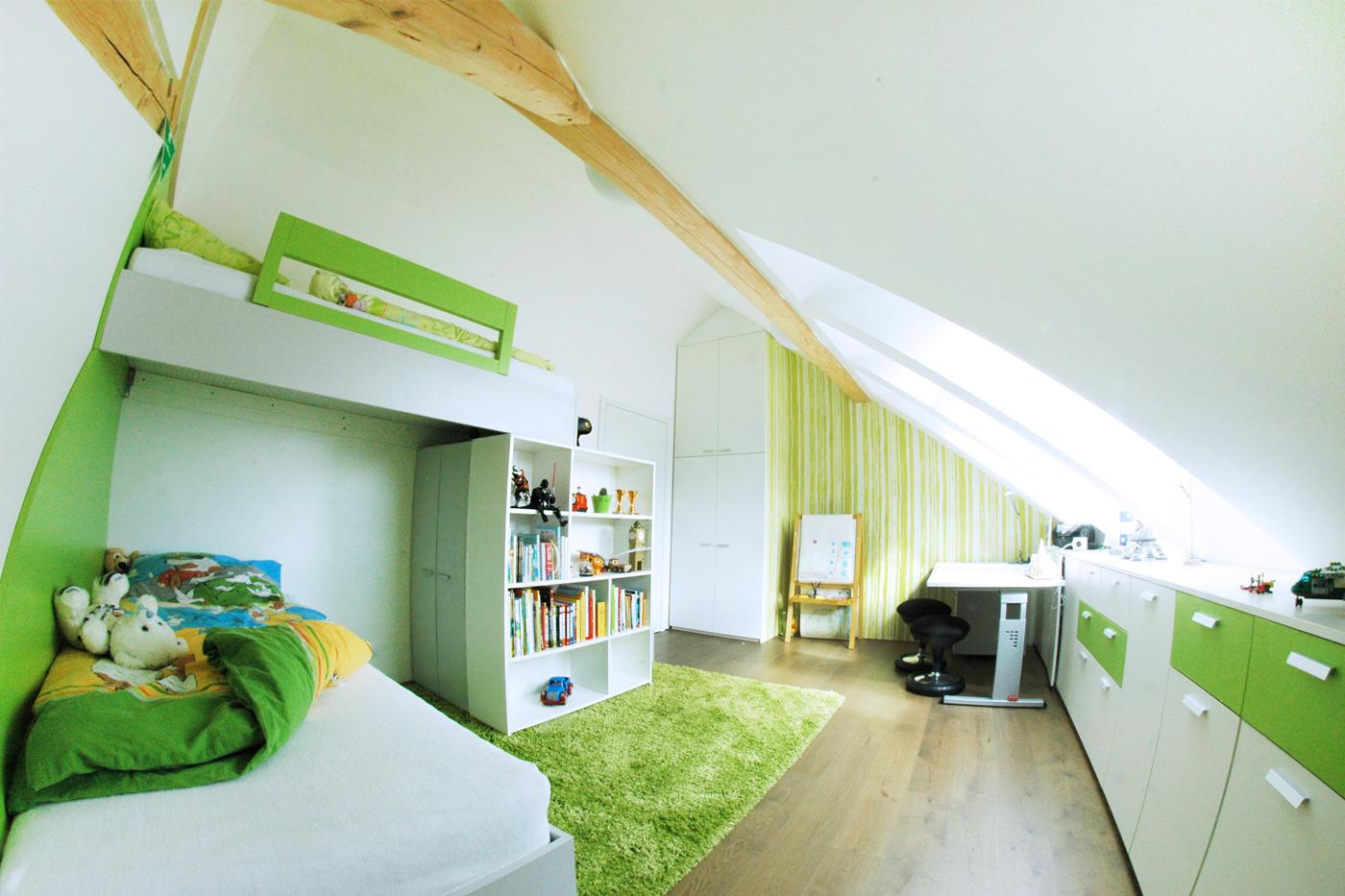 Po celé délce pokoje v místě, kde je nejnižší strop, jsou umístěné komody se šuplíky nebo dvířky.