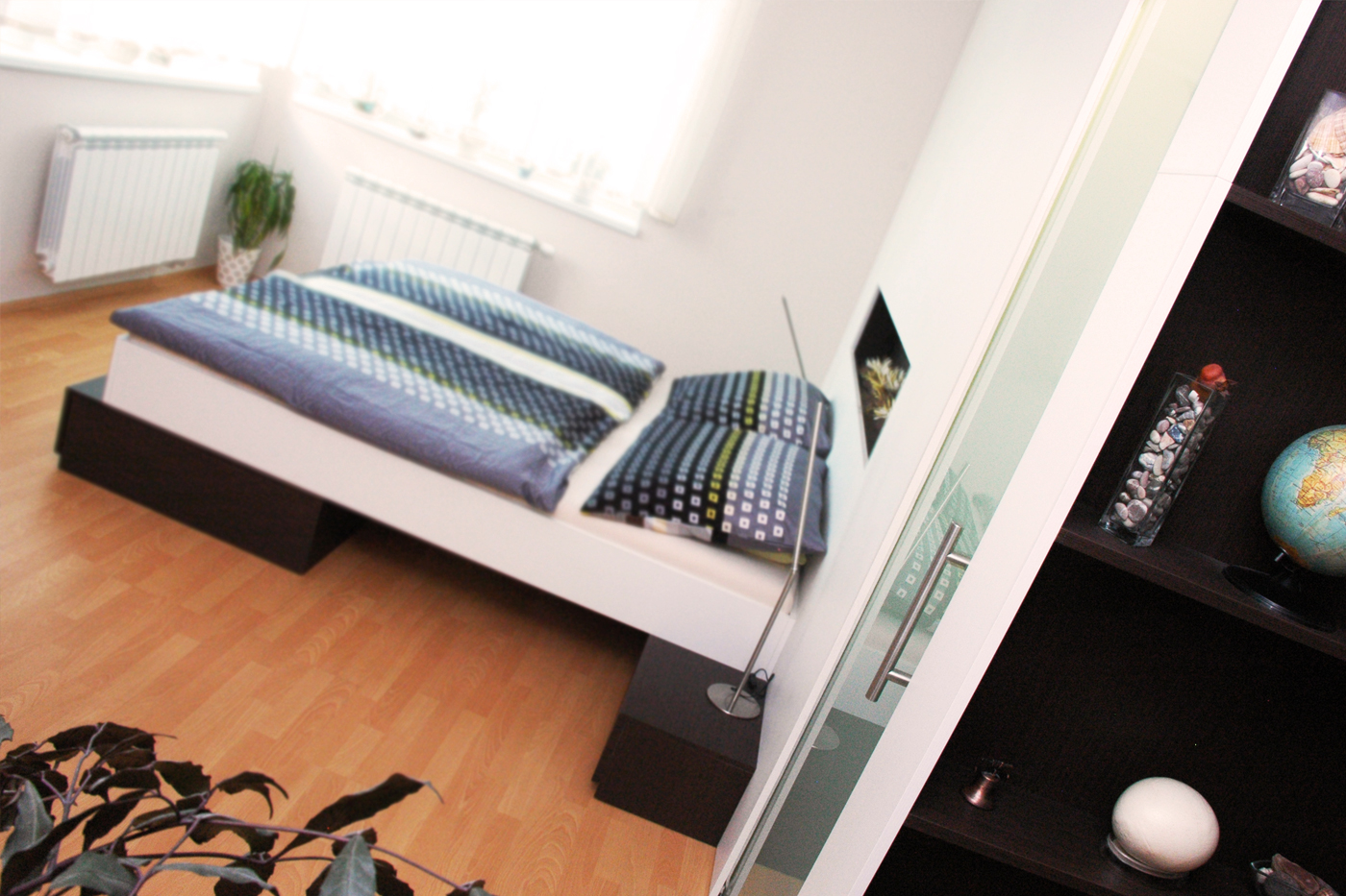 Rám postele leží na dvou kvádrech, které fungují jako noční stolky se šuplíky a velký šuplík pro lůžkoviny.