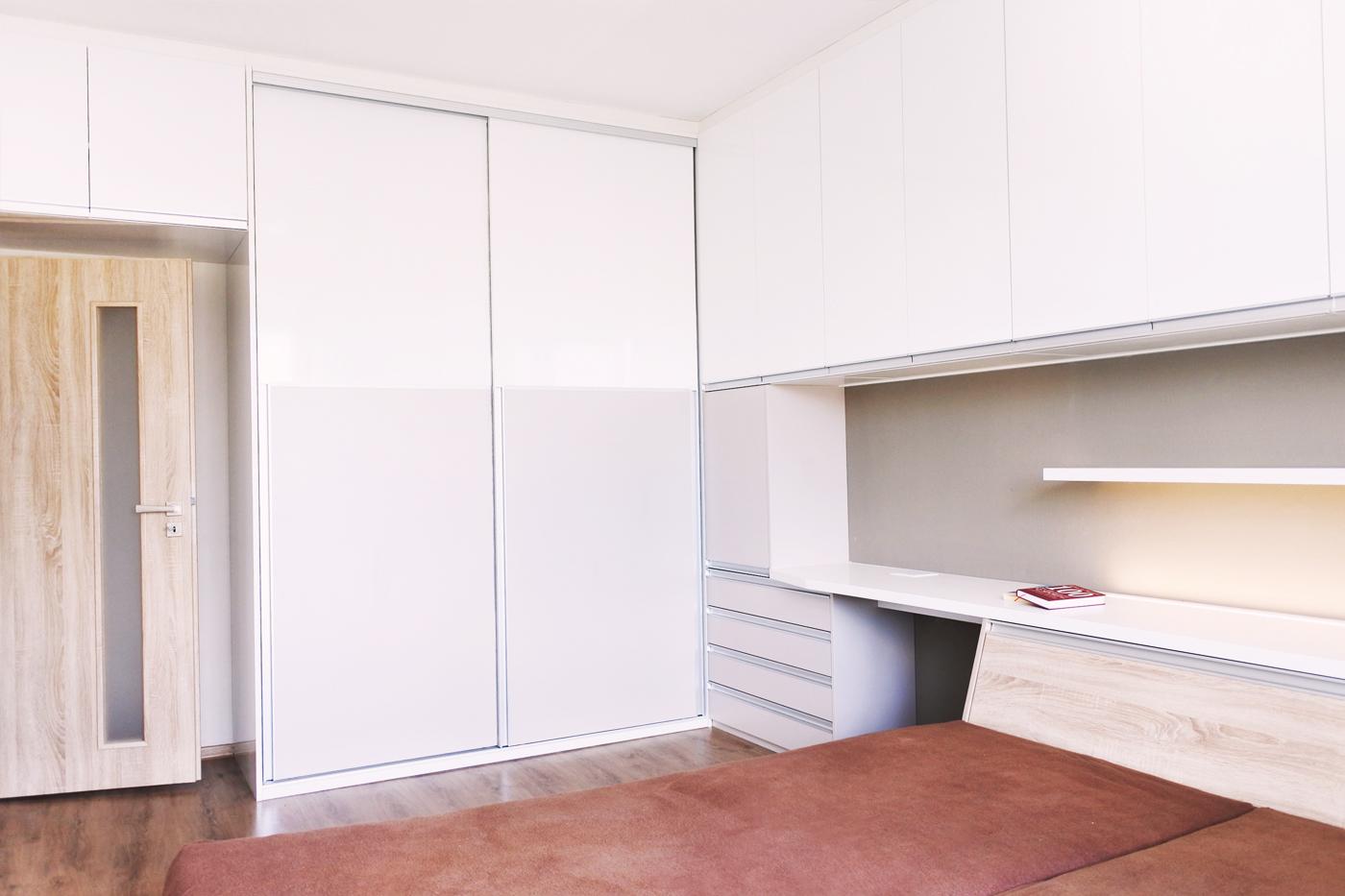 Úložný prostor pokračuje přes roh, kde tvoří šatní skříň. Díky tomu, že je hmota nábytku v rohu místnosti, působí prostor ložnice vzdušně.